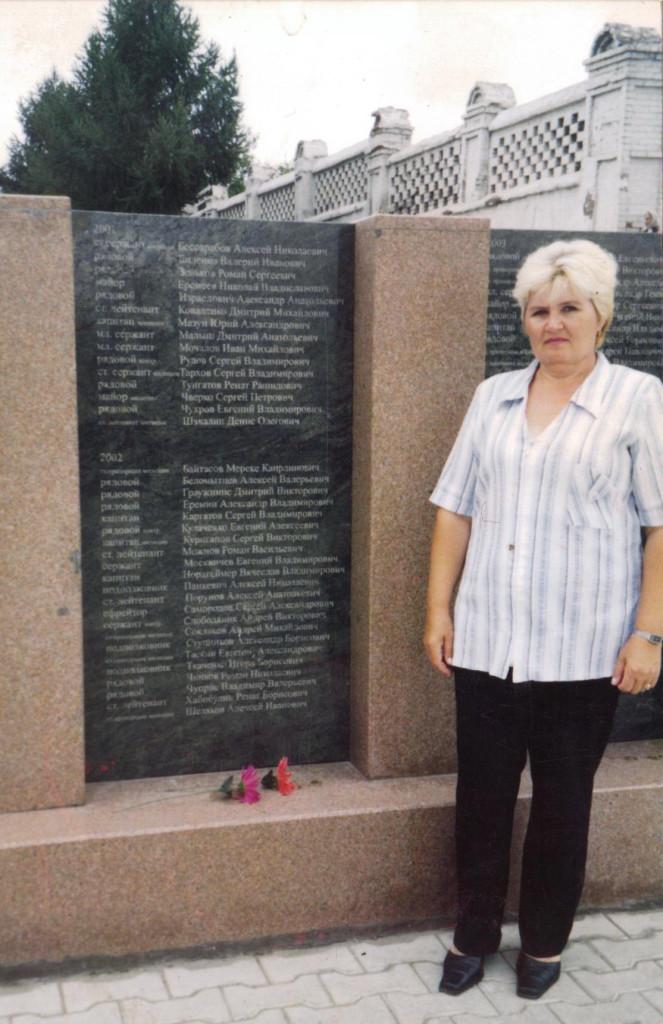 Нина Александровна рядом с мемориальной доской